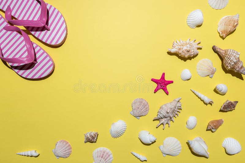 Creative composition with seashells and beach slippers on bright yellow background. Summer minimal concept.  royalty free stock image