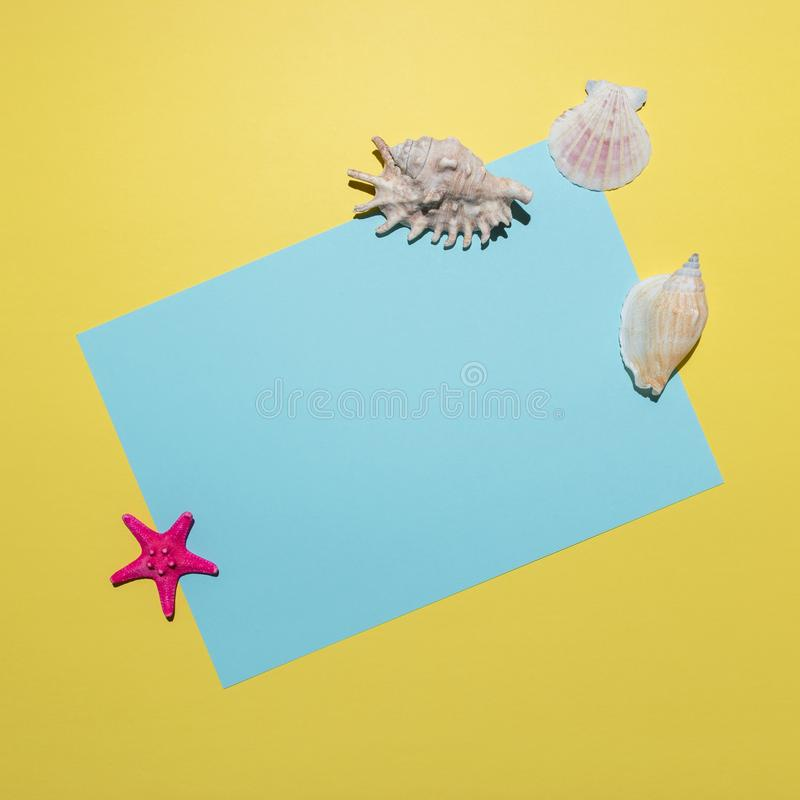 Creative composition with seashells and blue paper card on bright yellow background. Summer minimal concept.  royalty free stock photo