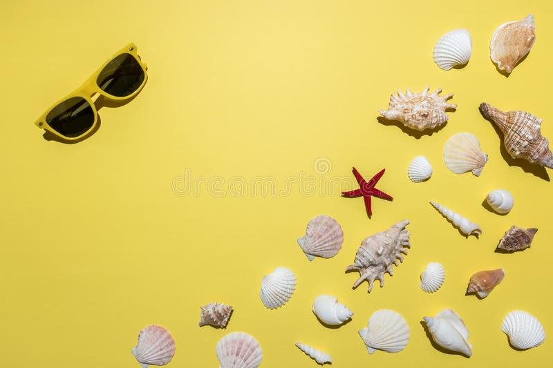 Creative composition with seashells and sunglasses on bright yellow background. Summer minimal concept.  royalty free stock images