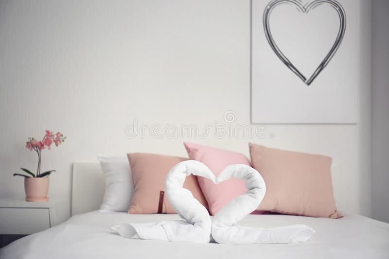 Creative composition with swans made of white terry towels on bed indoors stock photo