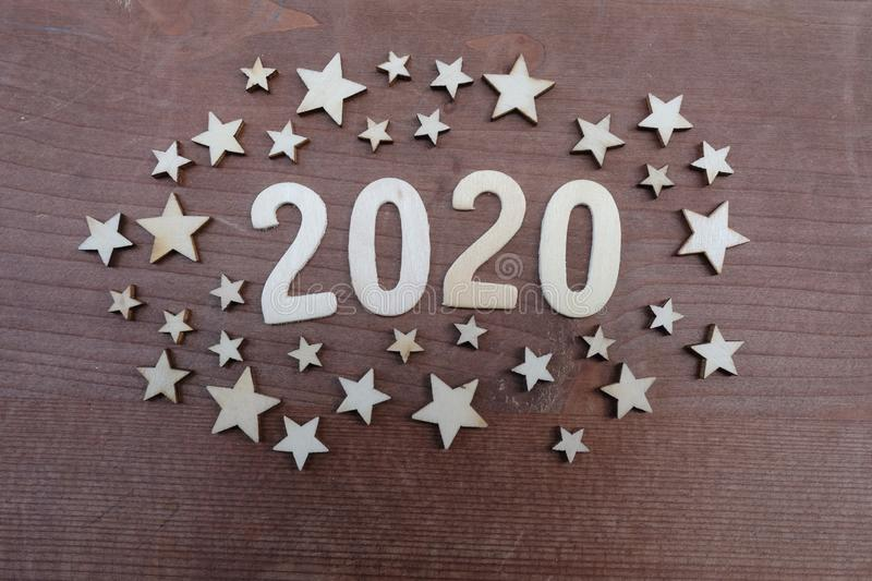 Year 2020 celebration with a wooden art composition with numbers and stars design stock photo