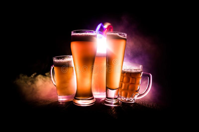 Creative concept. Beer glasses on wooden table at dark toned foggy background. Selective focus royalty free stock image