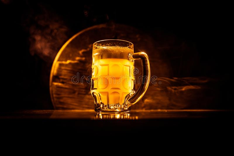 Creative concept. Beer glasses on wooden table at dark toned foggy background. Creative concept. Single beer glass on wooden table at dark toned foggy background stock image