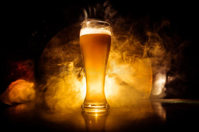 Creative concept. Beer glasses on wooden table at dark toned foggy background. Creative concept. Single beer glass on wooden table at dark toned foggy background royalty free stock photography