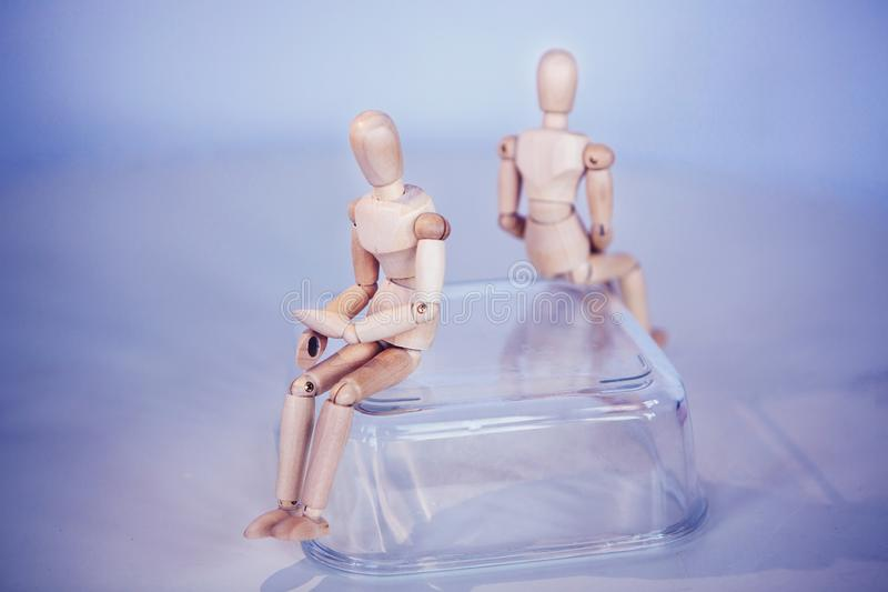 Creative concept. Conflict of interest.Wooden men sits on opposite sides. stock photo