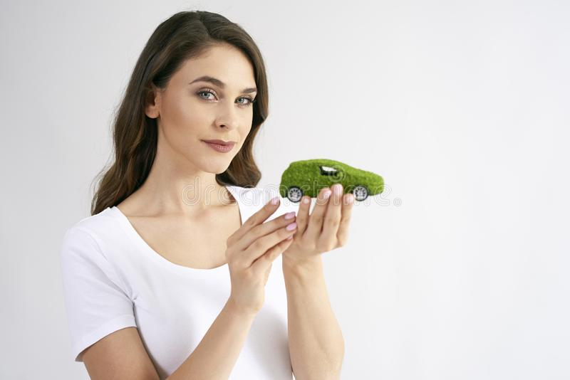 Creative concept of eco friendly car. Portrait of young woman holding model of eco friendly car in studio shot stock image