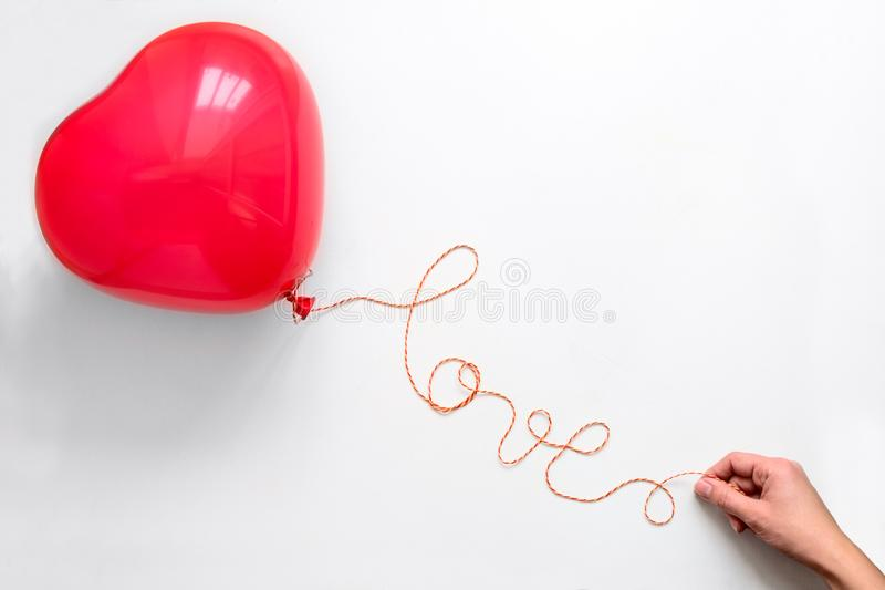 Creative concept. Hand holding red heart shape balloon with Love word from thread on white wooden background. Flat lay. Top view. stock photography