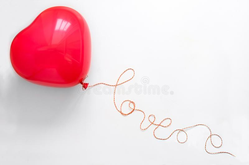 Creative concept. Hand holding red heart shape balloon with Love word from thread on white wooden background. Flat lay. Top view. stock image