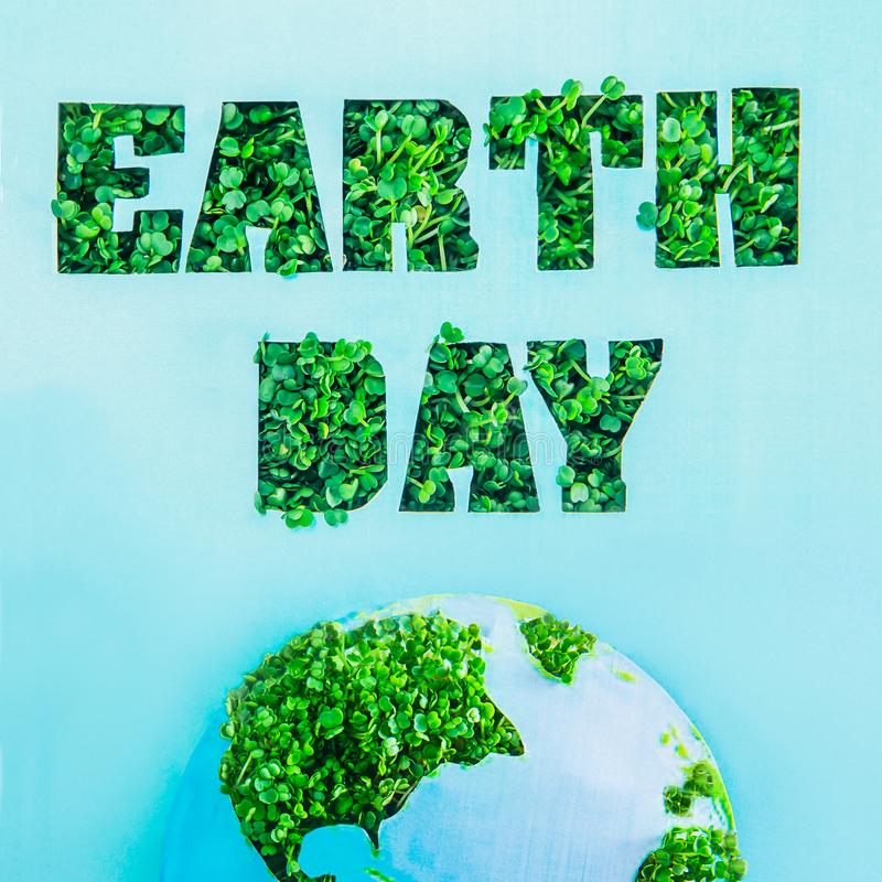 Creative concept with outline lettering Earth Day in green fresh grass sprouts and part of planet model on blue background. Save p stock image