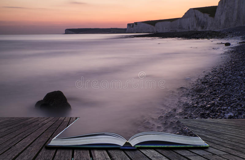 Creative concept pages of book Long exposure landscape rocky shoreline at sunset stock photos