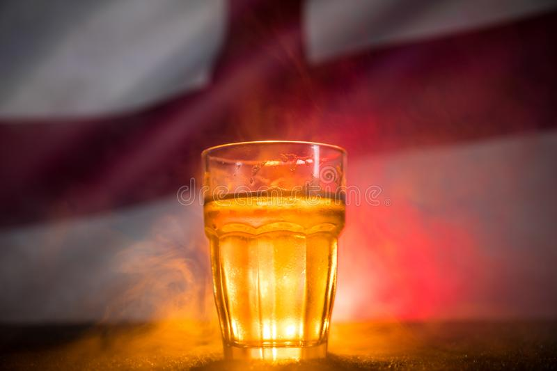 Creative concept. Pint of fresh beer on grass with blurred flag of England on background or Glass of lager beer ready for drink. C stock photography