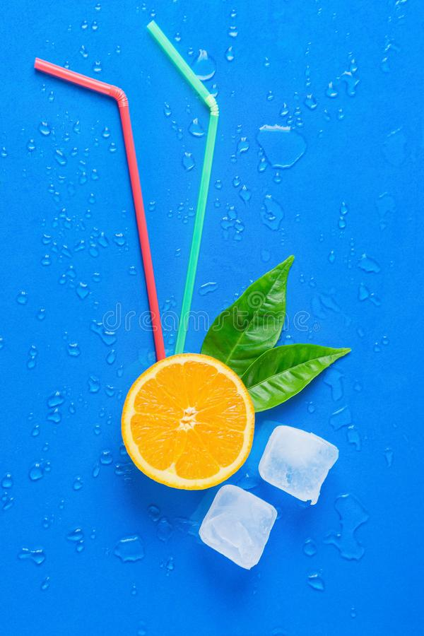 Ripe Juicy Cut in Half Orange Green Leaves Drinking Straws Melting Ice Cubes on Blue Background. Fresh Juices Summer Cocktails. Creative Conceptual Flat Lay Ripe royalty free stock photos