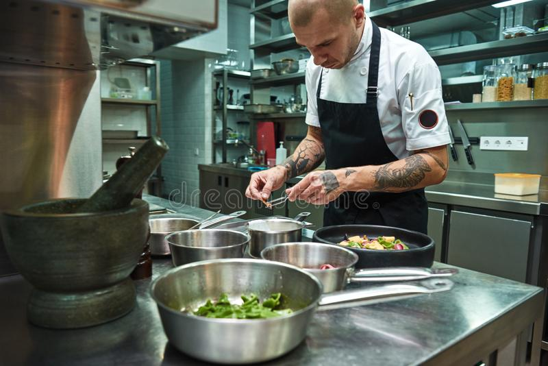 Creative cooking. Confident chef with several tattoos on his arms garnishing italian pasta in a restaurant kitchen stock images