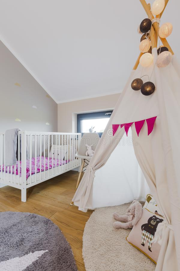 Creative cozy child rrom with teepee. Toys and baby cot royalty free stock images