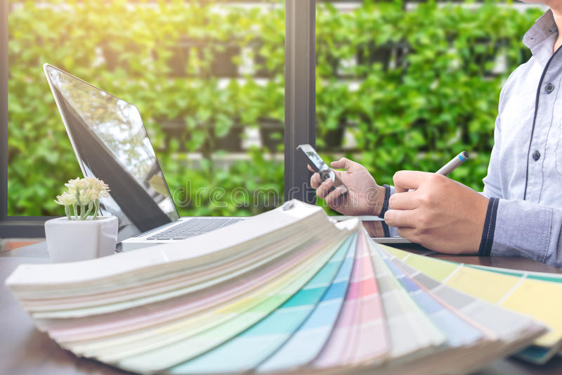 Creative creativity graphic designer working with graphics table. T,laptop and smart phone, colour chart at workplace on wooden desk , colour ideas style concept stock photo
