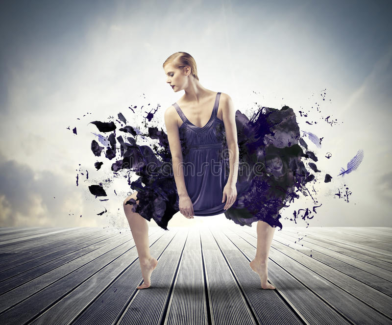 Creative dance. Beautiful woman dancing on a wood floor with her dress melting away royalty free stock image