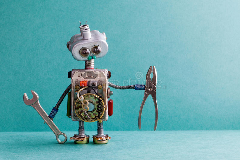 Creative design electrician robot with hand wrench pliers. Funny toy mechanic character lamp bulb eyes head, electric. Wires, capacitors vintage resistors royalty free stock photography