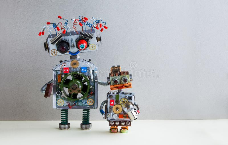 Robotic family. Big robot electrical wire hairstyle, plug arm. Small kid cyborg with lamp bulb toy. Copy space, gray. Creative design Robotic family. Big robot royalty free stock image