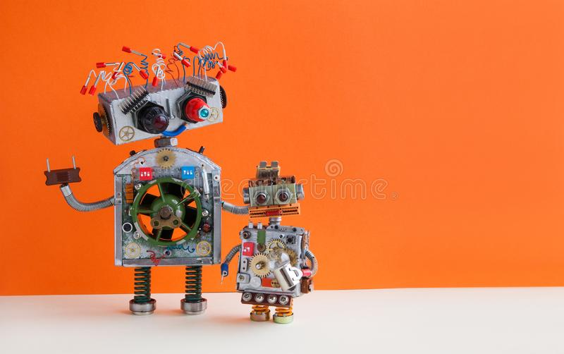 Creative design Robotic family. Big robot electrical wire hairstyle, plug arm. Small kid cyborg with lamp bulb toy. Copy. Space, orange wall background royalty free stock photography
