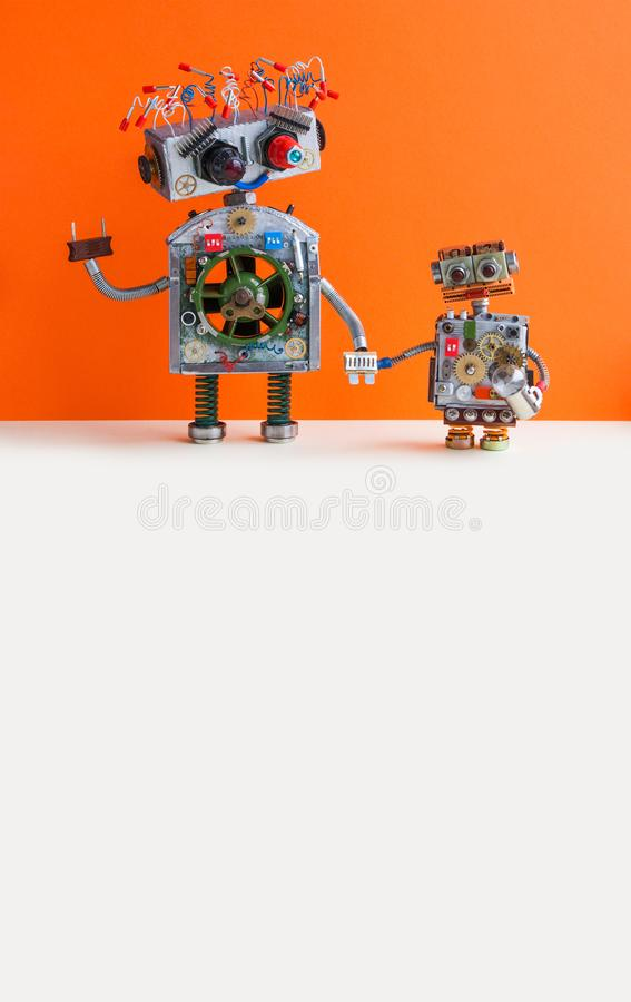 Creative design Robotic family. Big robot electrical wire hairstyle, plug arm. Small kid cyborg with lamp bulb toy. Orange wall, white floor background. Copy stock photo