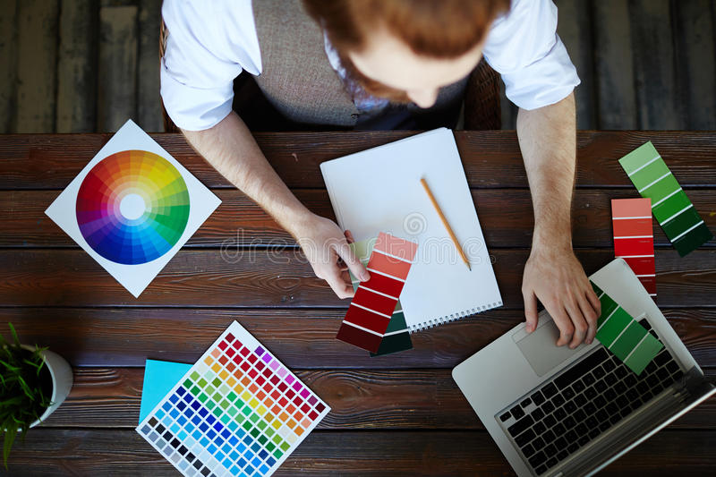 Creative Designer Choosing Color Scheme. Directly above view portrait of creative designer working in modern studio, choosing color scheme from swatches and royalty free stock photo