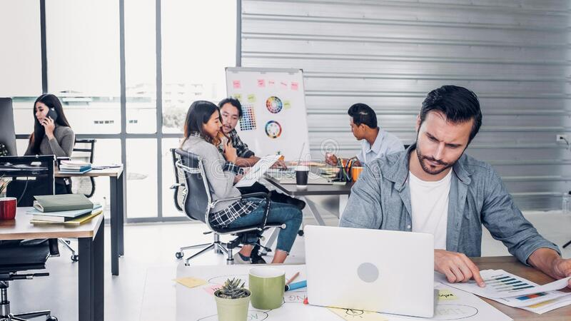 Creative designer director checking work on laptop while team is in casual meeting at background in modern office.agency lifestyle. Working concept stock photo