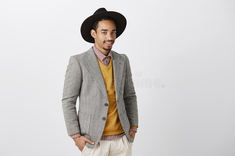 Creative designer discussing fashion show. Good-looking dark-skinned male model in stylish jacket and hat, standing half royalty free stock image