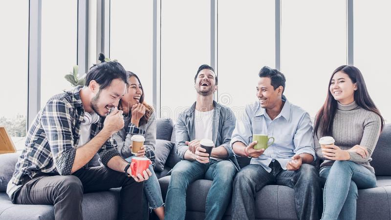 Creative designer take coffee break at office cafeteria. multiethnics employee sitting at sofa and talking and have fun.  stock photo