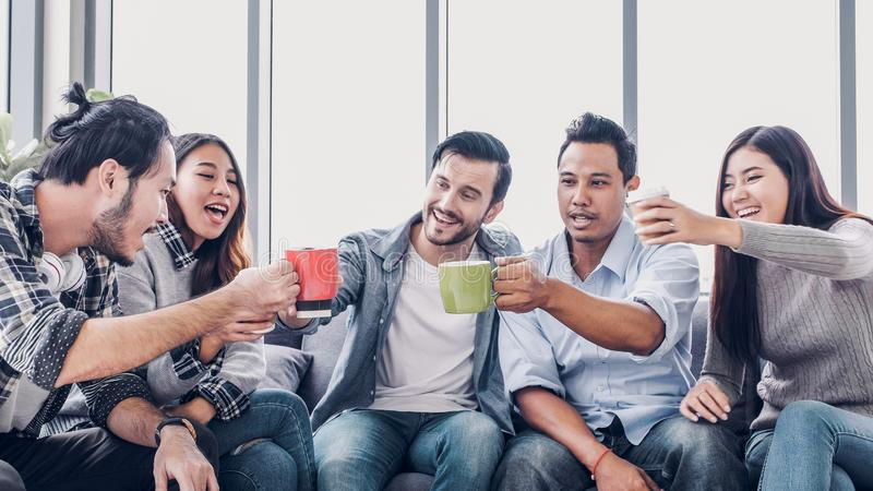 Creative designer take coffee break and toasting coffee cup at office cafeteria. multiethnics employee sitting at sofa and talking. And have fun royalty free stock images