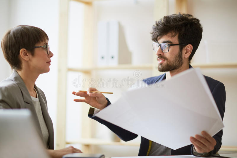 Creative Designner Explaining Project to Manager. Portrait of bearded creative men holding heap of paper gesturing actively while explaining project details to stock photos