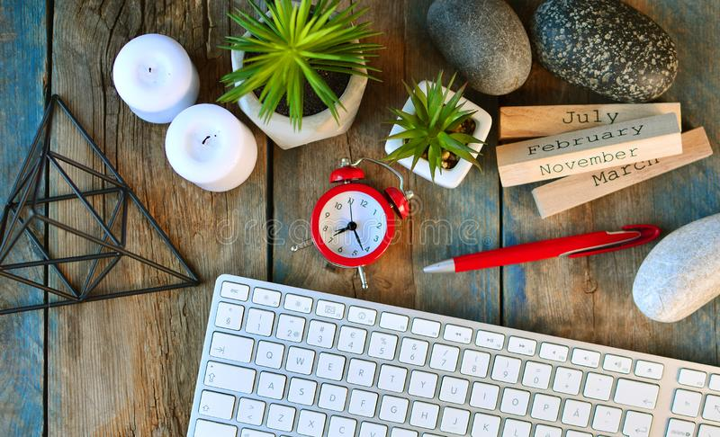 Creative desktop mess of creative person. Clock, computer keyboard, pen, flowers, prism figure, candles, stones and calendar on a wooden table royalty free stock photo