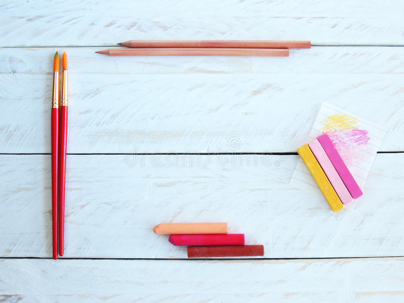 Creative desktop with pastels, brushes and wooden pencils. Styled stock photography with wooden pencils, paintbrushes, and soft and oil pastels, on a painted royalty free stock photos