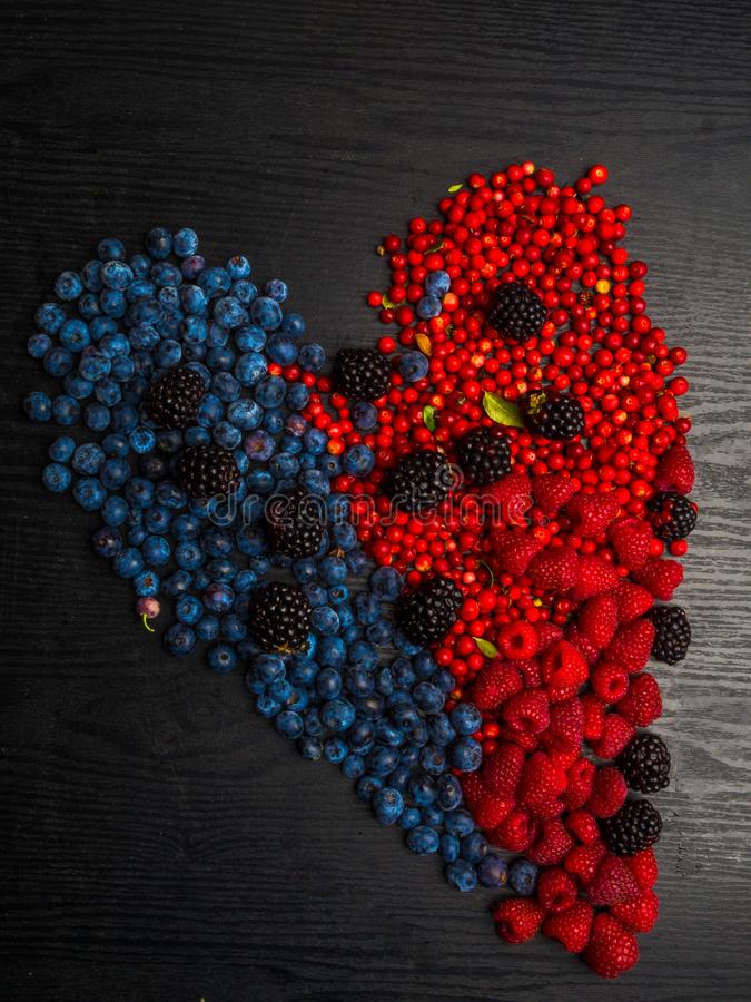 Creative diet food healthy eating concept photo of heart made of fresh summer berries full of vitamins as a symbol of romance love stock photo