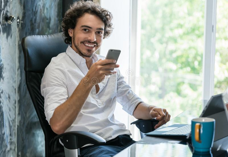 Creative director in agency with smartphone. Looking into camera royalty free stock photography