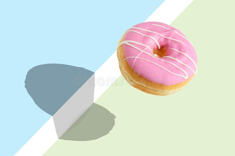 Creative disposition of pink donut on bright background. Minimal food concept stock photos