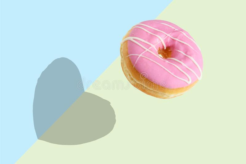 Creative disposition of pink donut on bright background. Minimal food concept stock photography