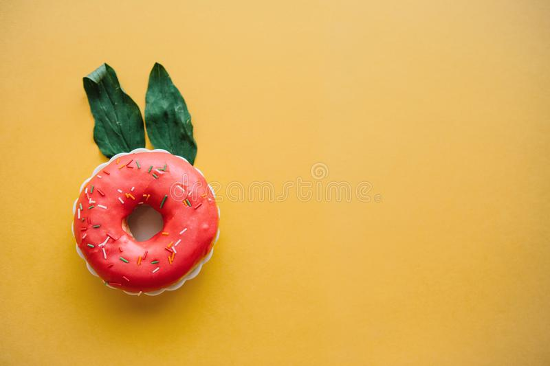 A creative donut with ears of leaves resembling a rabbit on a yellow background in a minimal style stock photography