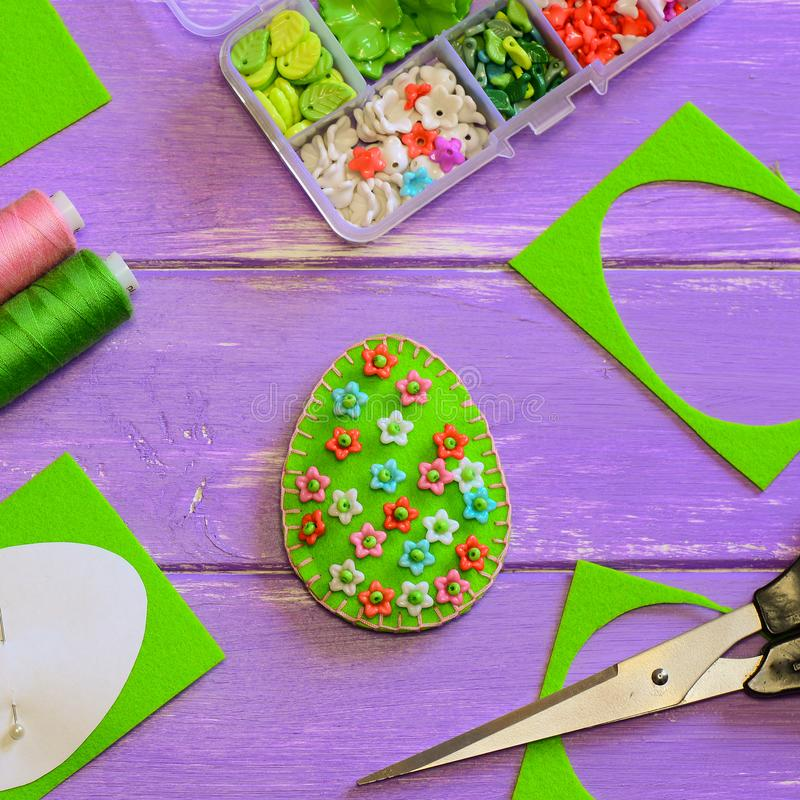 Creative Easter egg decoration with plastic flowers. Felt egg with floral pattern, scissors, paper template stock photography