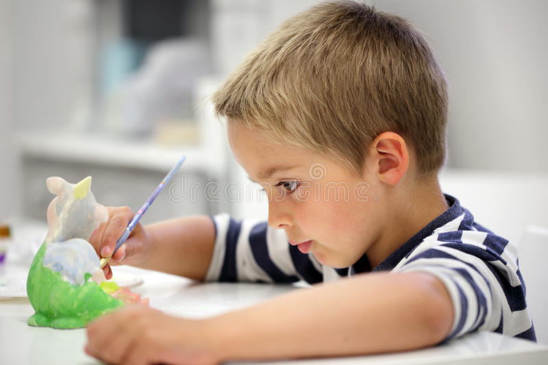 Creative education. Child painting a ceramic pottery model at school concept for art and creative education