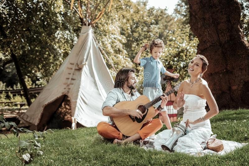 Creative family playing musical instruments near tent stock photos