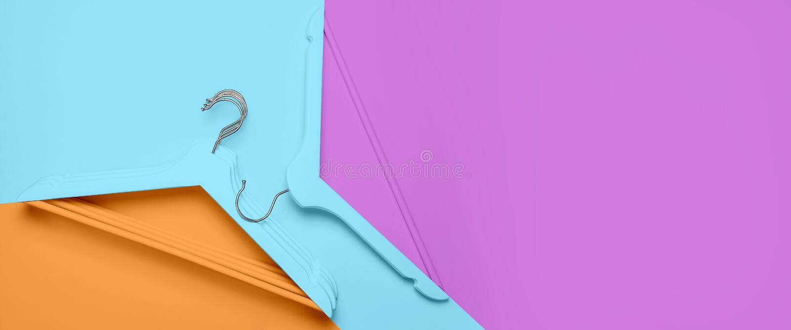 Creative fashion concept. Flat lay top view colored wooden hangers on blue pink orange neon background minimalism style. Pop-art. Sale discount store shopping royalty free stock image
