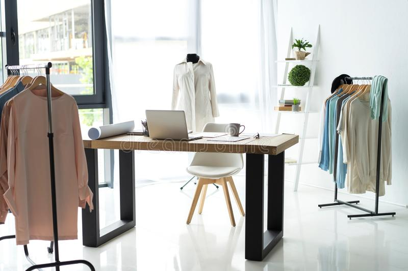 Creative fashion designer desk or workplace with sewing equipment, fabrics, templates, modern stylist inspirational. Office, dressmaker atelier with mannequin royalty free stock image