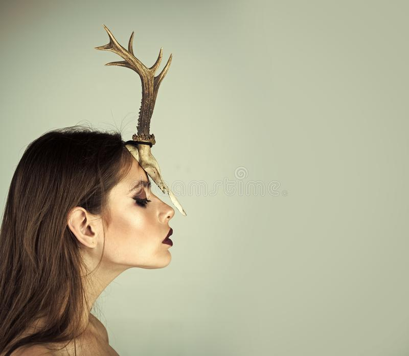 Creative fashion photography. Woman with makeup and antlers. Fashion devil of mystic shaman girl with horns. Beauty look stock photo