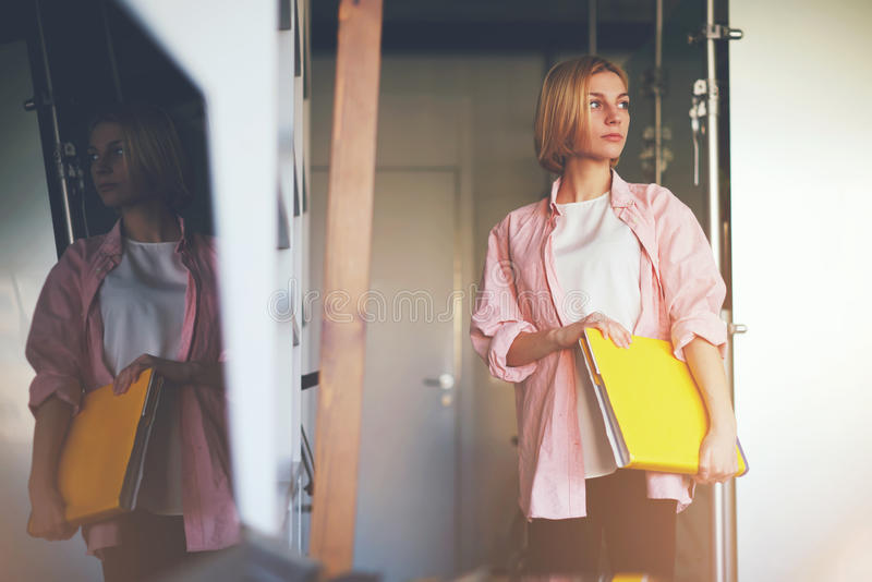 Creative female designer with big magazine catalog standing in her studio. Portrait of young stylish woman holding bright yellow book standing near shelf in home stock images