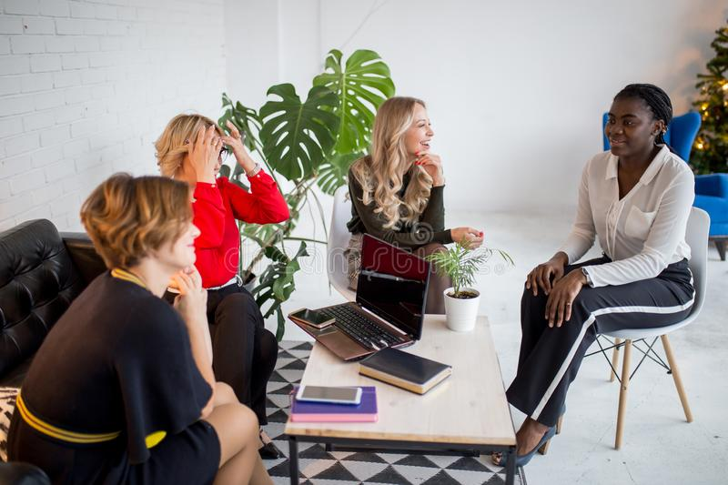 Happy multi-ethnic female friends meeting at hall after corporate training stock photo