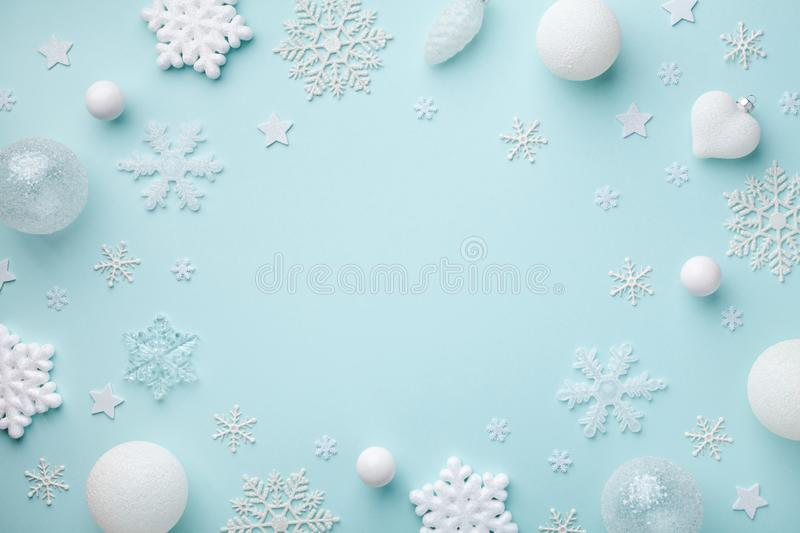 Creative festive frame with white holiday balls and decorative snowflakes on turquoise pastel background. Christmas card. Flat lay. Creative festive frame with royalty free stock photos
