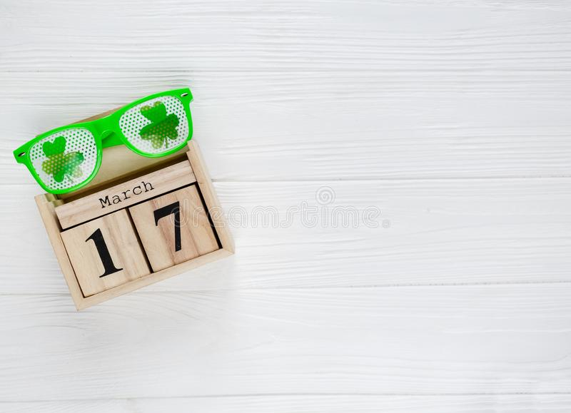 Creative festive St Patricks background with white light box calendar 17 march and fun green glasses with shamrock on whi. Te wooden table. Flat lay composition stock photography