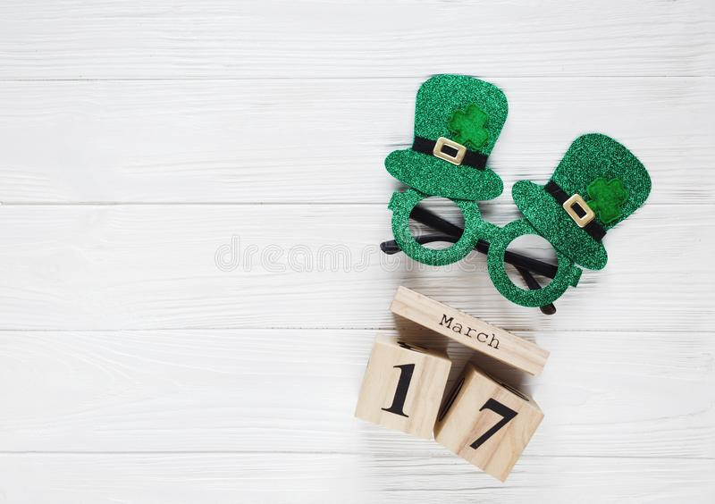 Creative festive St Patricks background with wooden calendar and glasses with shamrock on white wooden table. Flat lay copy space royalty free stock photography