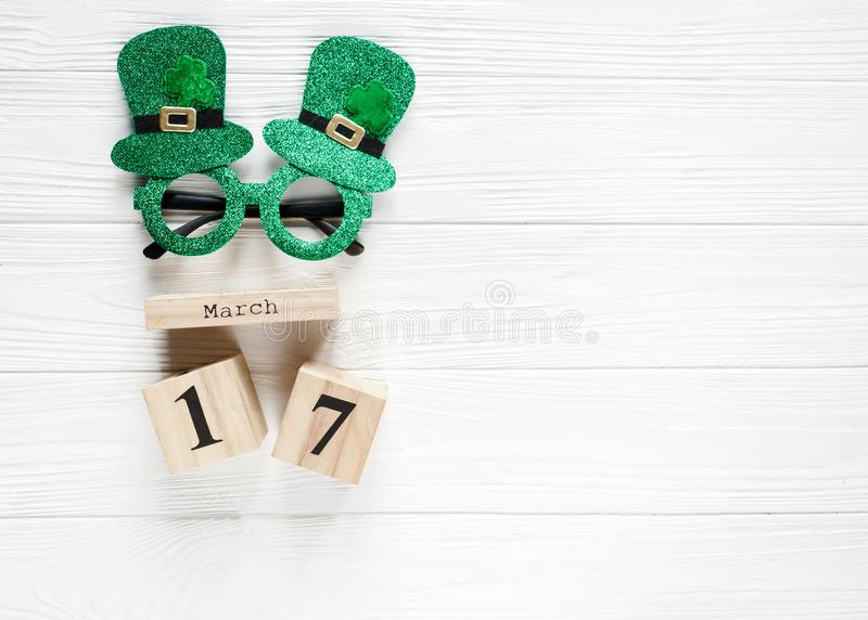 Creative festive St Patricks background with wooden calendar and glasses with shamrock on white wooden table. Flat lay. Copy space royalty free stock photography