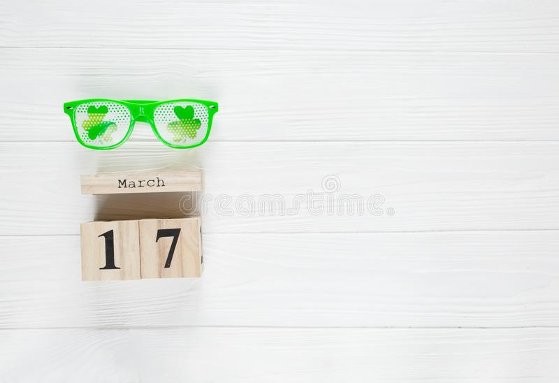 Creative festive St Patricks background with wooden calendar and glasses with shamrock on white wooden table. Flat lay copy space stock photography